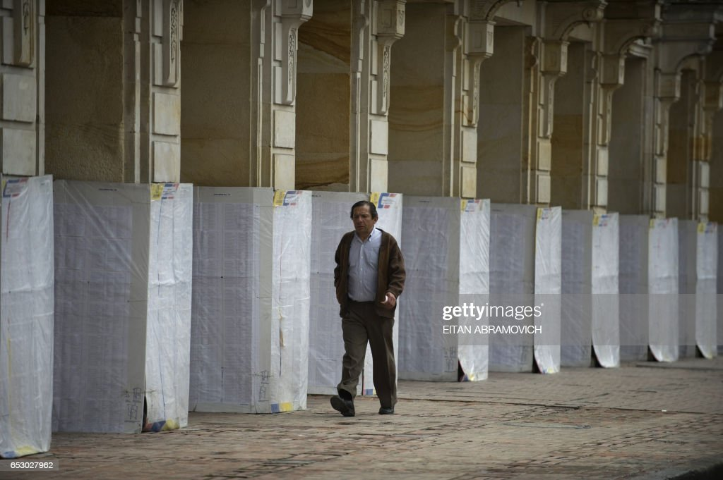 A man passes by electoral lists pasted on the walls at Bolivar Square in downtown Bogota, Colombia, on June 19, 2010. Nearly 30 million voters head to the polls Sunday to choose a successor to President Alvaro Uribe. The runoff pits frontrunner ex-defense minister Juan Manuel Santos and former two-time Bogota mayor Antanas Mockus. The two came out ahead in the first round of votes on May 30, but fell short of the 50 percent required for an outright win. AFP PHOTO/Eitan Abramovich /