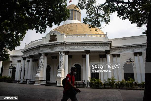 A man passes by empty National Assembly Building as a preventive measure against the new type of coronavirus pandemic in Caracas Venezuela on April...
