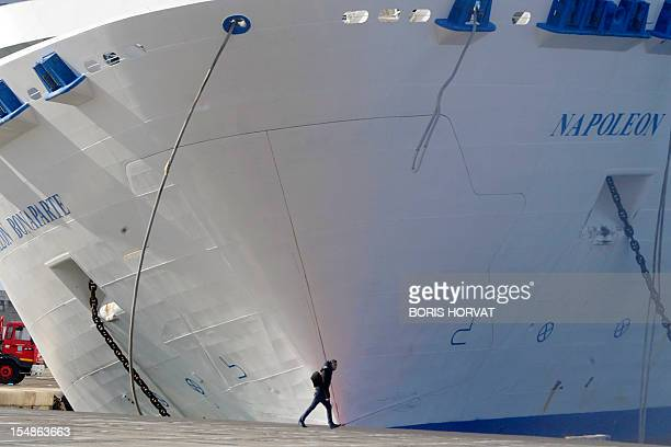 A man passes by the ferry NapoleonBonaparte of the French SNCM company which tilts to the side against a quay on October 28 2012 in Marseille's...