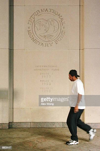 A man passes by the logo of International Monetary Fund September 28 2000 outside the IMF building in Washington