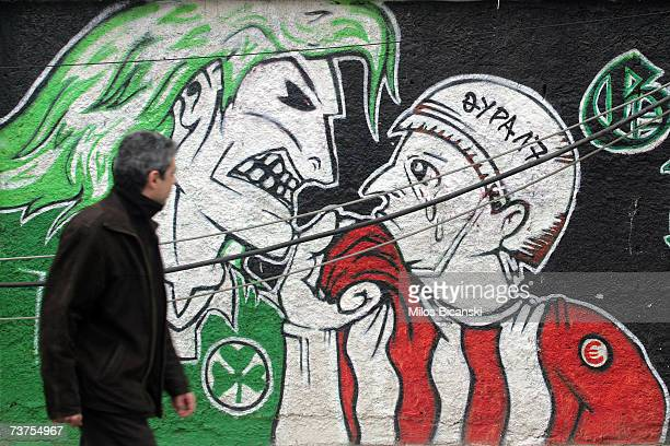 A man passes FC Panathenaikos Green Hools graffiti depicting hooliganism against FC Olympakos fans in the Piraeus suburb on March 31 2007 in Athens...
