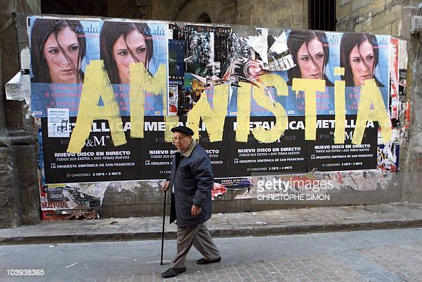 A man passes grafitti saying amnistia a reference to ETA members in jail in the streets of Bilbao Basque country in northern Spain 29 November 1999...