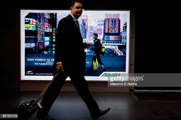 A man passes in front of a Alitalia advertising board in Linate airport during the strike of Alitalia workers in Linate airport on November 11 2008...