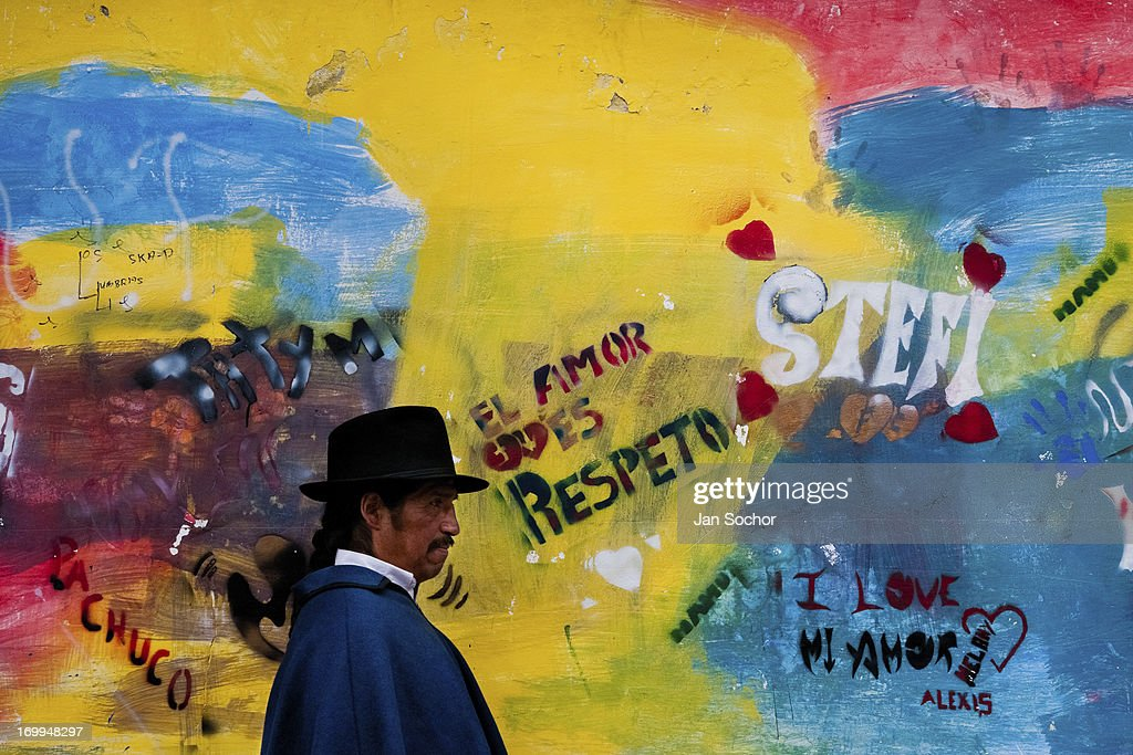 "A man passes in front of a colorfully paited wall during the Inti Raymi fiesta in Cotacachi, Ecuador, 29 June 2010. Inti Raymi, ""Festival of the Sun"" in Quechua language, is an ancient spiritual ceremony held in the Indian regions of the Andes, mainly in Ecuador and Peru. The lively celebration, set by the winter solstice, goes on for various days. The highland Indians, wearing beautiful costumes, dance, drink and sing with no rest. Colorful processions in honor of the God Inti (Sun) pass through the mountain villages giving thanks for the harvest and expressing their deep relation to the Mother Earth (Pachamama)."