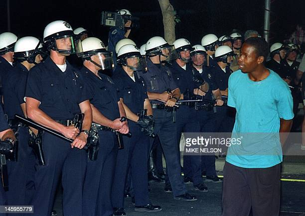 A man passes in front of a line of policemen in Los Angeles 30 April 1992 Riots broke out in Los Angeles after a jury acquitted four police officers...