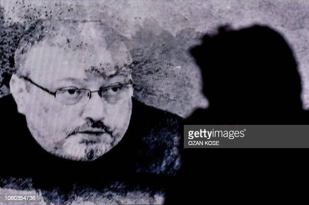 A man passes in front of a screen showing Jamal Khashoggi during a commemoration event of Khashoggi's supporters on November 11 2018 in Istanbul US...
