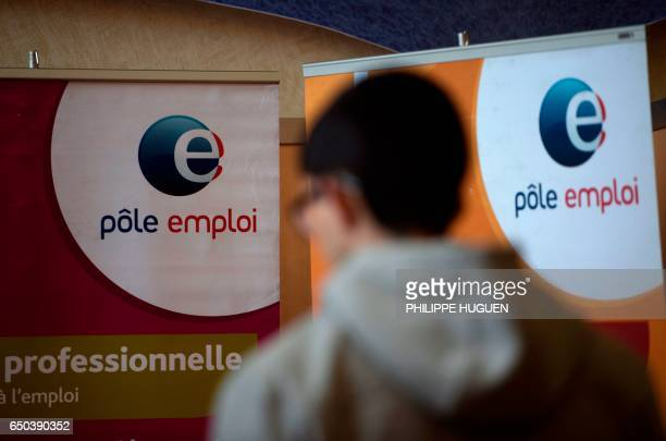 A man passes in front of an Pole Emploi panel on March 8 2017 in Dunkirk the French economy has created close to 190000 net positions in 2016 an...