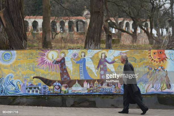 A man passes in front of the Art Work created by young children during a competition 'Golden Easel' featuring a magnificent 100meter canvas around...