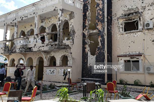 Man passes in front of the rubbles of the popular Medina hotel of Kismayo on July 13 a day after at least 26 people, including several foreigners,...