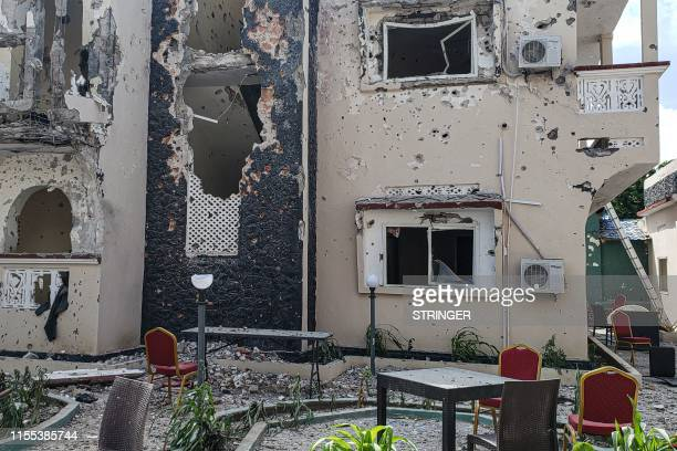 A man passes in front of the rubbles of the popular Medina hotel of Kismayo on July 13 a day after at least 26 people including several foreigners...