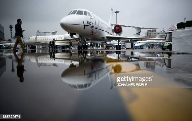 A man passes the Dassault Falcon 2000EX business jet before the start of the 2017 Asian Business Aviation Conference and Exhibition at Shanghai's...