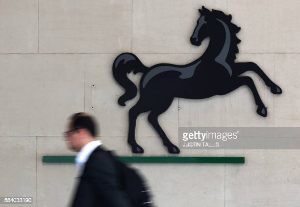 A man passes the entrance to a Lloyds Banking Group office in the City of London on July 28 2016 British bank Lloyds will axe 3000 more jobs by 2017...