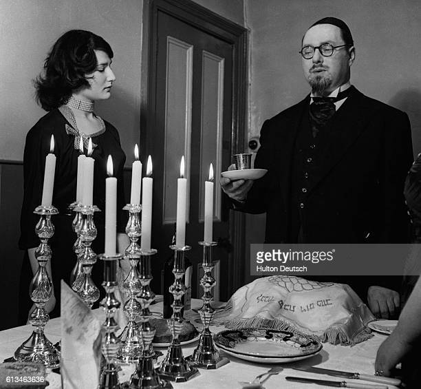 A man passes the Kiddush wine in the silver cup to a woman on the eve of the Sabbath during Passover