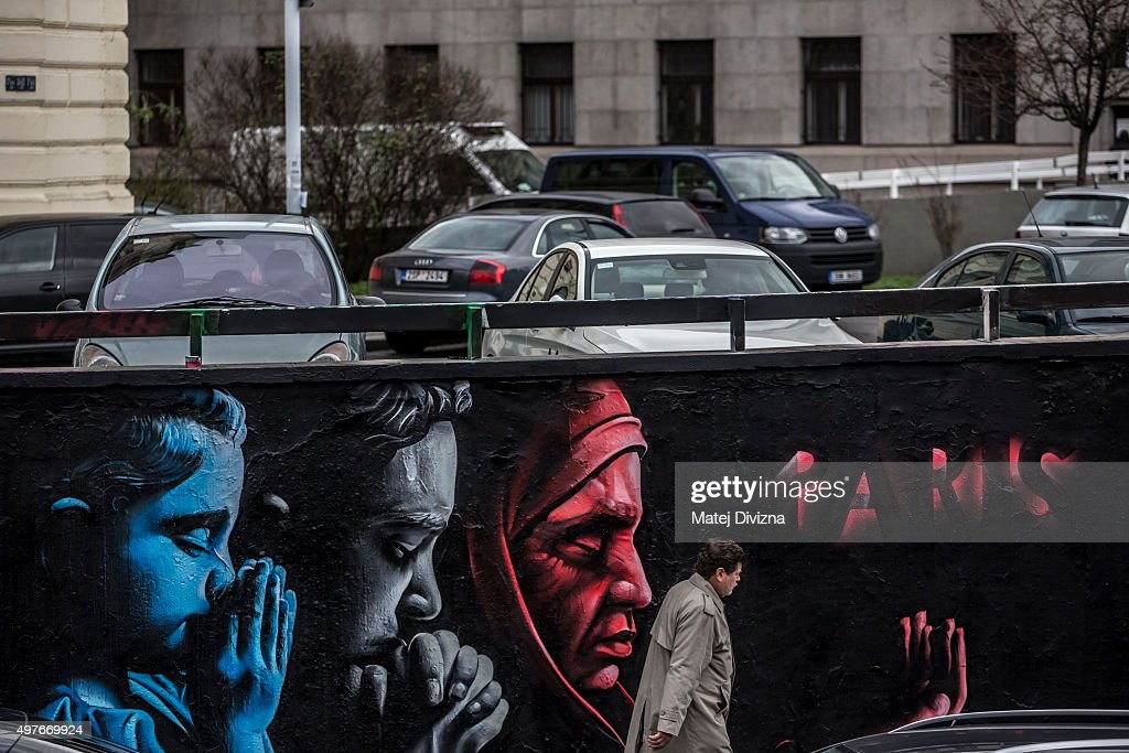A man passes the wall with graffiti to honour the victims of the Paris terrorist attacks by the Kazakhstani artist called ChemiS on November 18, 2015 in Prague, Czech Republic. People across the world commemorate the victims of the attacks last Friday in Paris that left 130 people dead across the French capital.