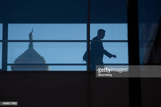 A man passes through a walkway between an office building and parking garage with the Liberty Building in the background in Buffalo New York US on...