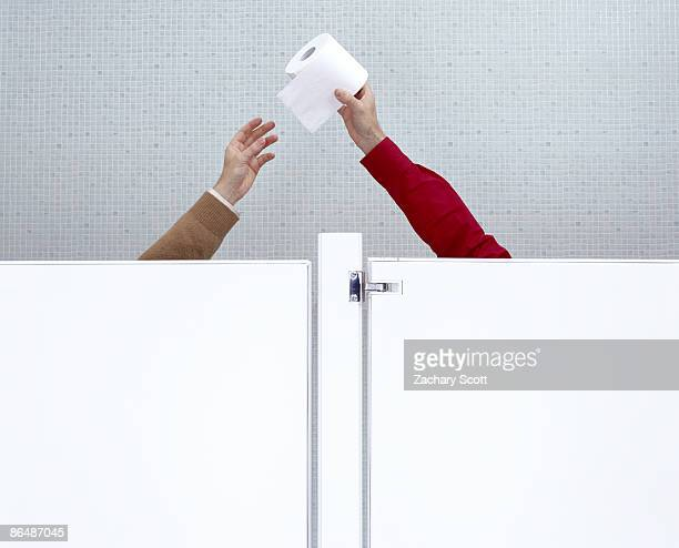 man passes toilet paper from one stall to another - 単語 help ストックフォトと画像