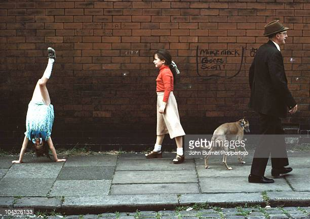 A man passes two little girls on a street in Manchester England in 1976