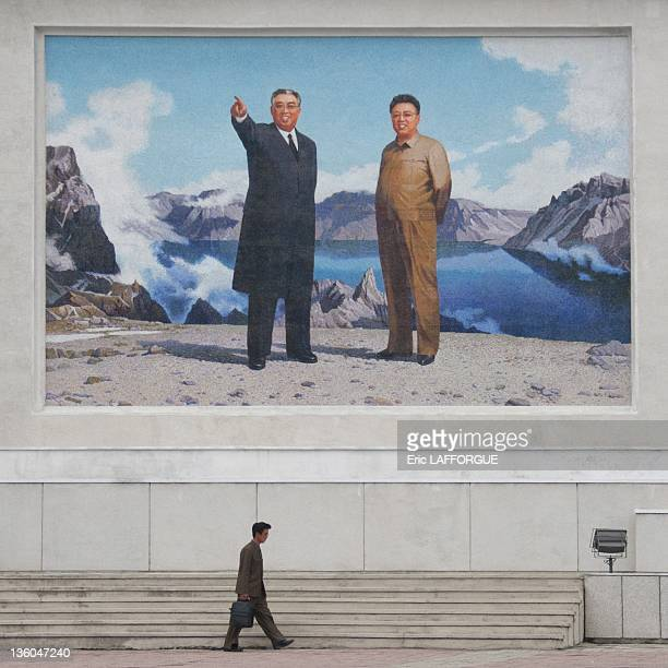 A man passes underneath a giant poster of leaders Kim Il Sung and Kim Jong Il on September 14 2011 in Wonsan North Korea