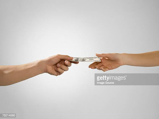 Man passing banknote to woman