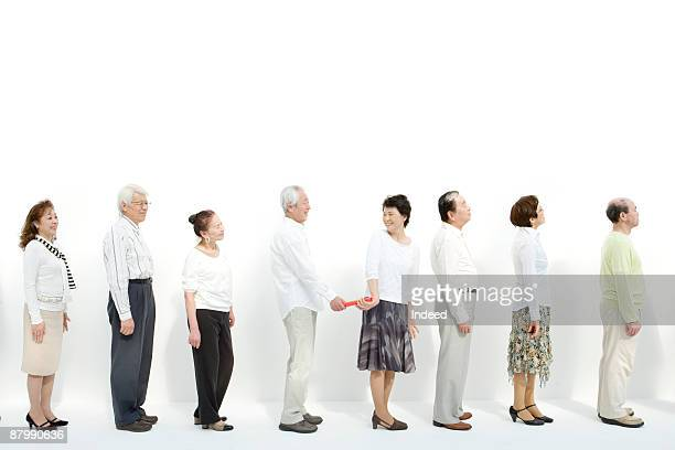man passing baton to woman in a row - passing sport imagens e fotografias de stock