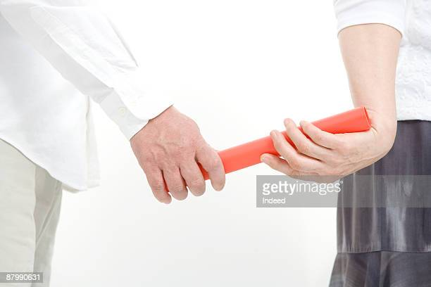 Man passing baton to woman, mid section