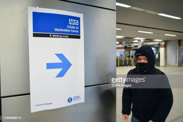 Man passing by a sign, with directions to recently opened NHS Vaccination Centre at Wembley. The site is located near Wembley Stadium, in the Olympic...