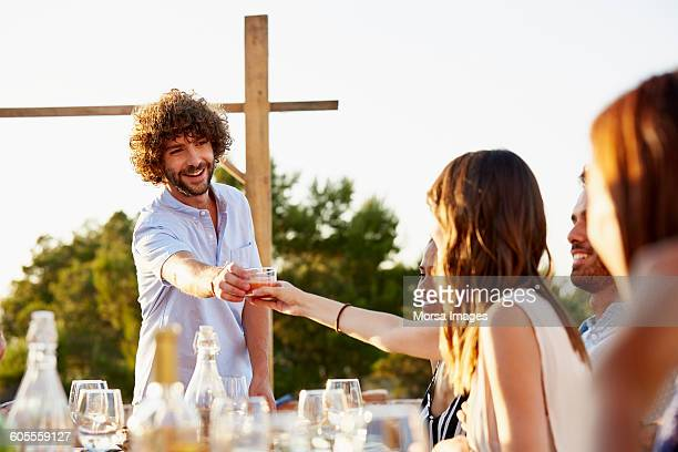 Man passing drink to friend at social gathering