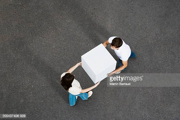 man passing giant white cube to woman, elevated view - 運ぶ ストックフォトと画像