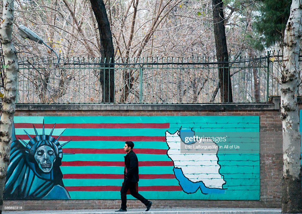 Man Passing In Front Of Anti-american Mural Propoganda Slogan Depict Statue Liberty Skeleton On The Wall Of The Former United States Embassy, Central District, Tehran, Iran : News Photo