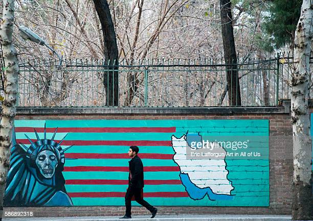 Man passing in front of antiamerican mural propoganda slogan depict statue liberty skeleton on the wall of the former united states embassy central...