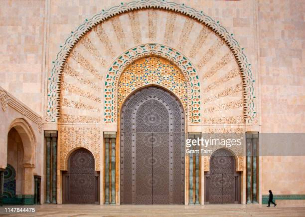 man passing main entrance to mosque. - casablanca morocco stock pictures, royalty-free photos & images