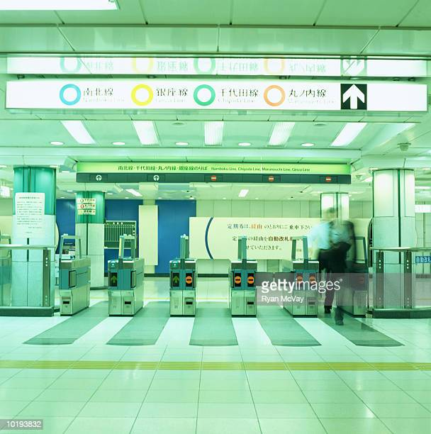 Man passing through turnstile in subway station (blurred motion)