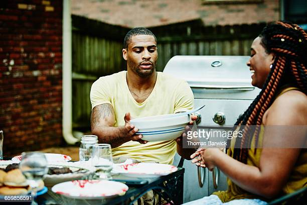 Man passing woman bowl of salad during dinner