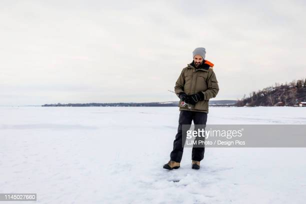 man patiently waiting for a bite while ice fishing at wabamun lake - ice fishing stock pictures, royalty-free photos & images