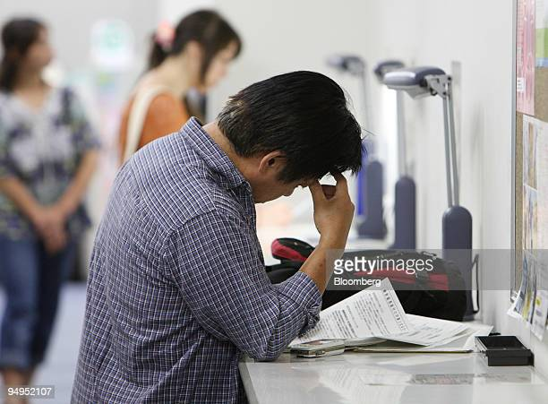 A man pauses as he searches job listings at Ikebukuro Hello Work a job center in the Toshima Ward in Tokyo Japan on Friday Aug 28 2009 Japan's...