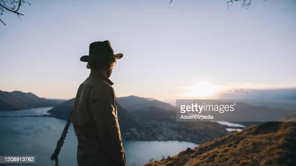 man pauses at edge of trail, mountainside - homens de idade mediana imagens e fotografias de stock