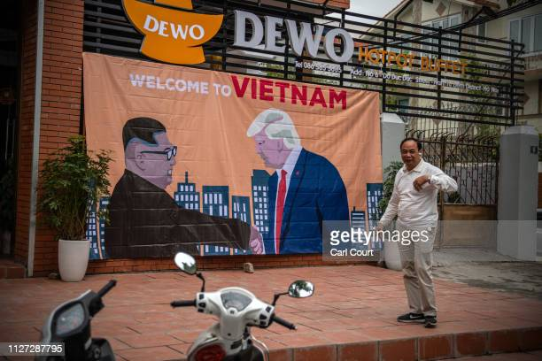 A man pauses by a banner showing US President Donald Trump and North Korean leader Kim Jongun shaking hands next to the words 'Welcome to Vietnam'...