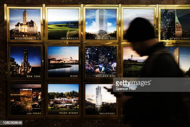A man pauses in front of pictures of Trump properties in Trump Tower in midtown Manhattan on December 10 2018 in New York City President Donald...