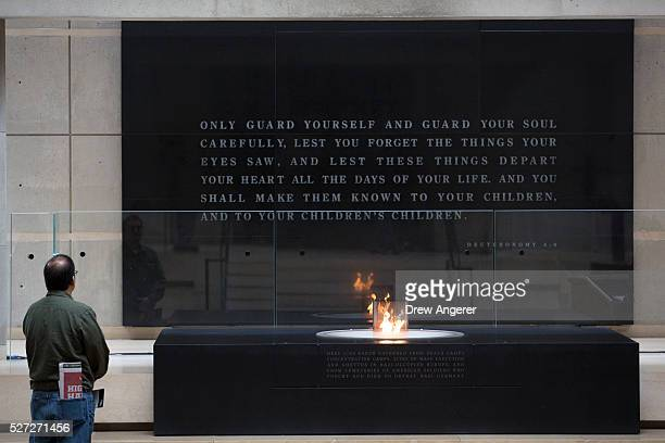 A man pauses in front of the eternal flame during the annual Names Reading ceremony to commemorate those who perished in the Holocaust in the Hall of...