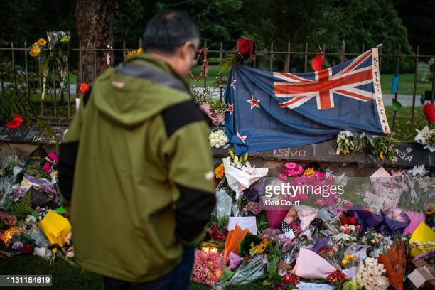A man pauses next to a New Zealand flag hung amongst flowers and tributes on the wall of the Botanic Gardens on March 17 2019 in Christchurch New...