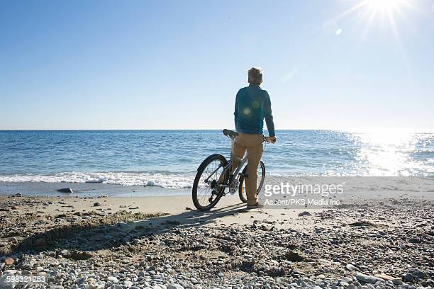 Man pauses on bicycle at beach edge, looks to sea