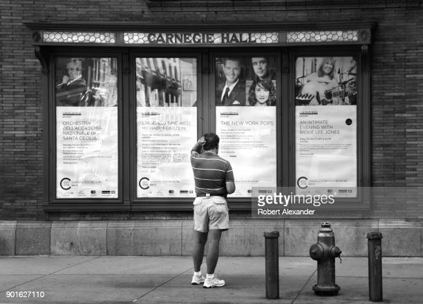 Man pauses to read posters announcing upcoming concerts at Carnegie Hall in New York City.
