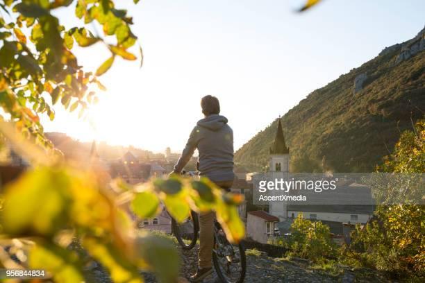 mann hält mit dem fahrrad über finalborgo bei sonnenaufgang - dorf stock-fotos und bilder