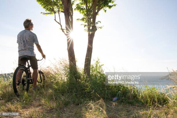 Man pauses with bicycle at viewpoint, looks over sea