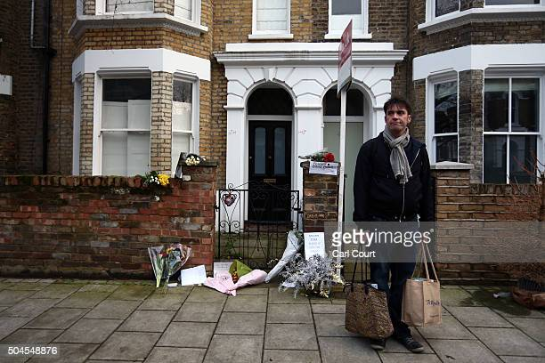 A man pauses with his shopping as he visits the boyhood home of David Bowie in Brixton where people have left flowers and tributes on January 11 2016...