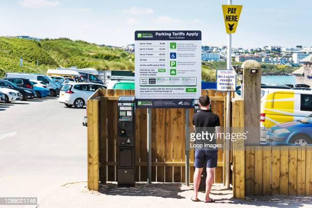 Man paying a parking fee at the car park in Fistral in Newquay in Cornwall.