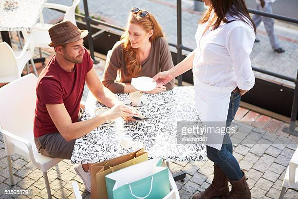 Man paying bill in a pavement cafe