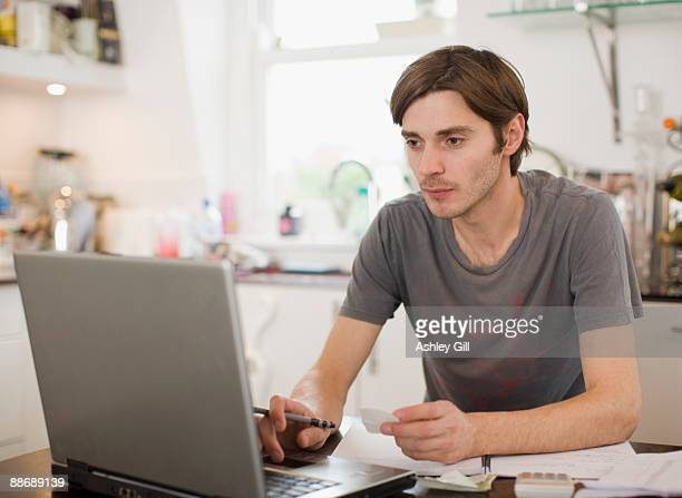 man paying bill on laptop in kitchen - one mid adult man only stock pictures, royalty-free photos & images