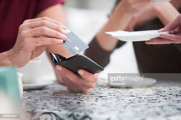 Man paying bill with credit card in a pavement cafe