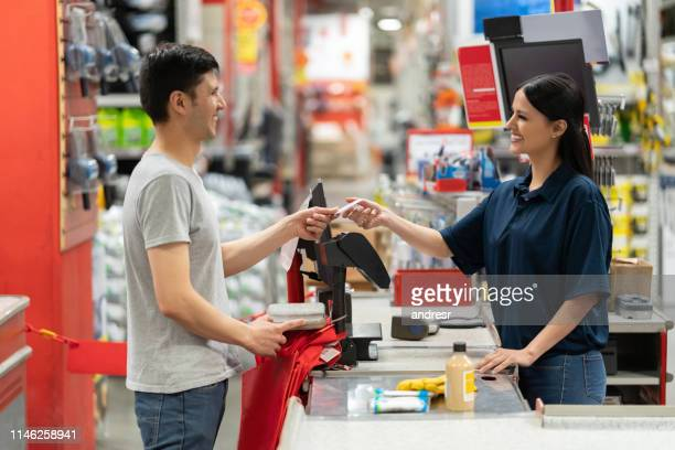 homem que paga pelo cartão no caixa em uma loja da melhoria home - material - fotografias e filmes do acervo